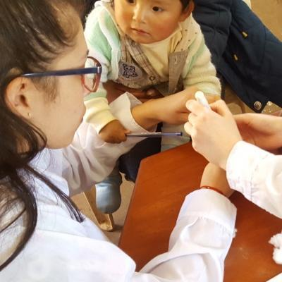 Two students doing Midwifery internships in Peru test an infant's iron levels at a clinic.